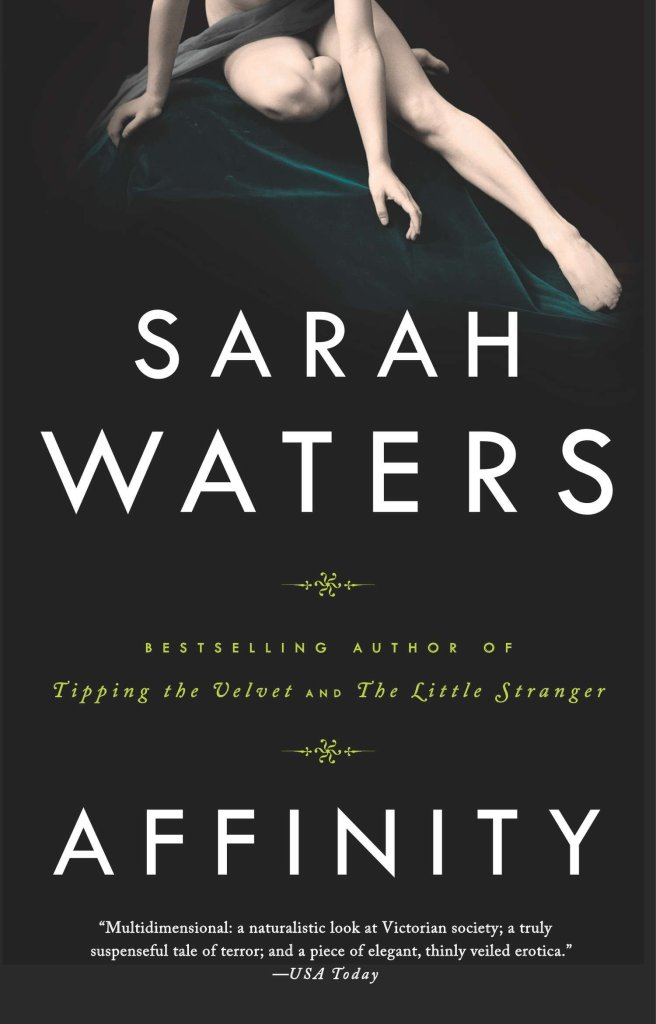 Cover of Affinity by Sarah Waters. A mostly naked, very pale woman is shown perched on a bench covered in draped green velvet fabric. The woman has a sash of fabric covering her lap, and is only visible from the waist down.