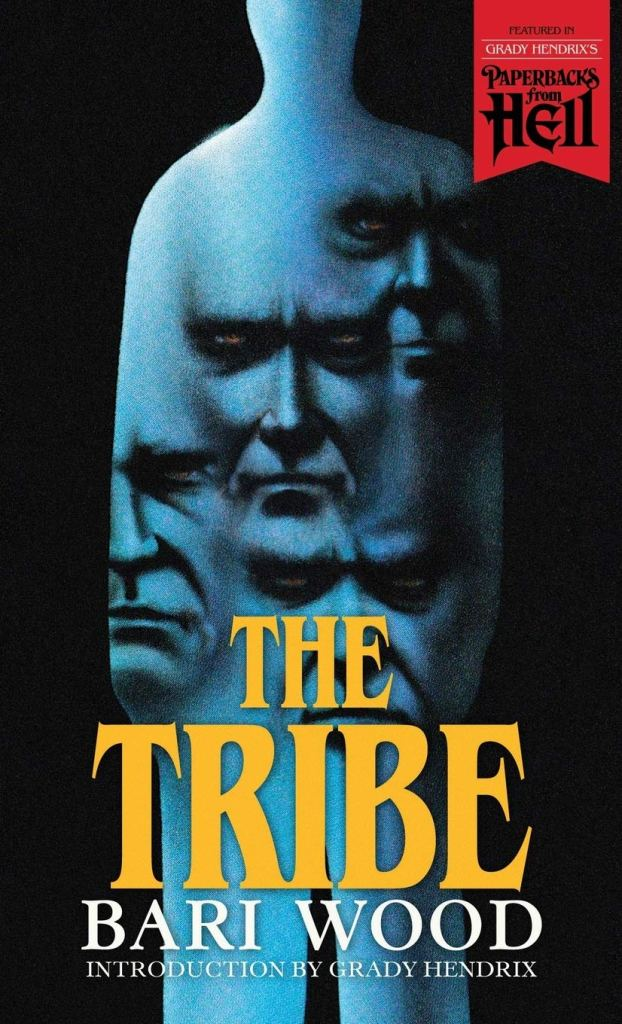 Cover of The Tribe by Bari Wood. Cover shows a blue silhouette, shaped only like the rough outline of a man. Repeated images of the same face over and over are hovering inside the silhouette.