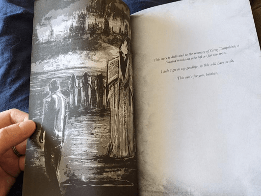 HOWLer @RyanMarie opens a paperback copy of The Final Reconciliation to a beautiful black and white art piece featuring The Yellow King with hooded, shadowy figures and the ruins of a city in the background. A figure in the foreground looks at the King and shadowy figures. The dedication page of the book is also visible.