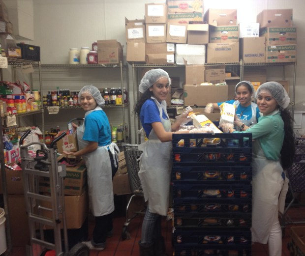 Youth organizing a pantry at a dining hall