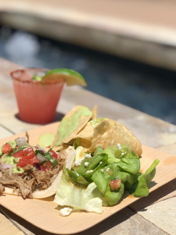 A close up photo of a pork taco, tortilla chips with guacamole, and small salad. There is a margarita drink next to the plate.