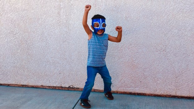 boy in an action pose wearing luchador mask