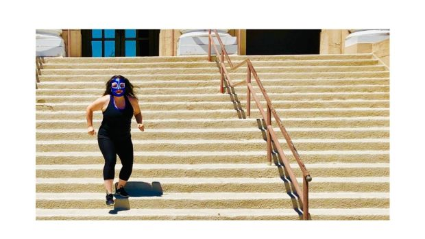 California woman running down steps in a luchador mask to vote on March 3
