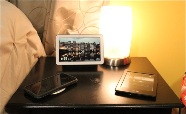 A Nest Hub, a wireless charger, a lamp with a smart bulb and a light.