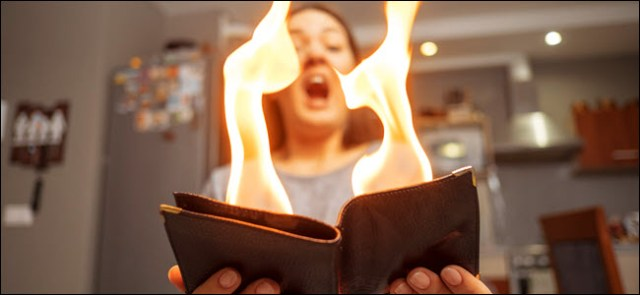 young woman holding a burning wallet