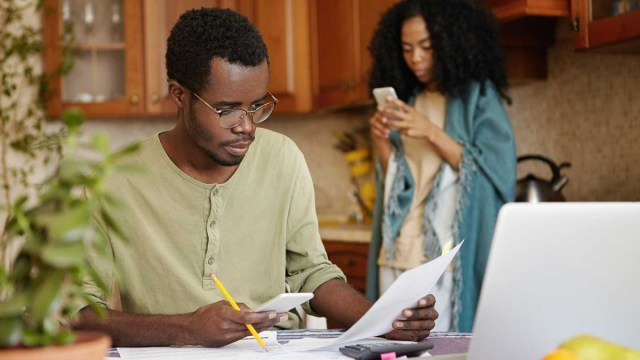 A man sitting at a kitchen table looking at a piece of paper and holding a pencil and a smartphone, and a woman in the background in pajamas looking at her phone.