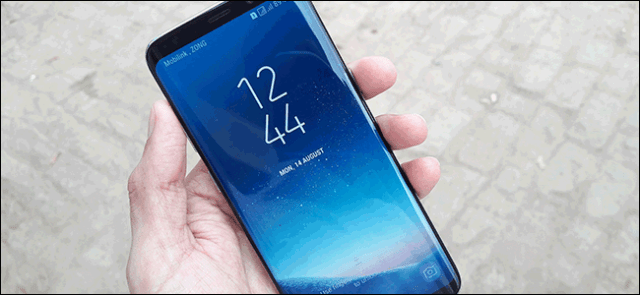 A hand holding a Samsung Galaxy S8 with the touch screen to display the time and date.