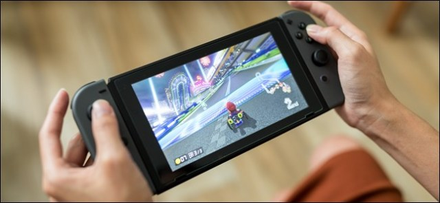 Hands holding a Nintendo Switch.