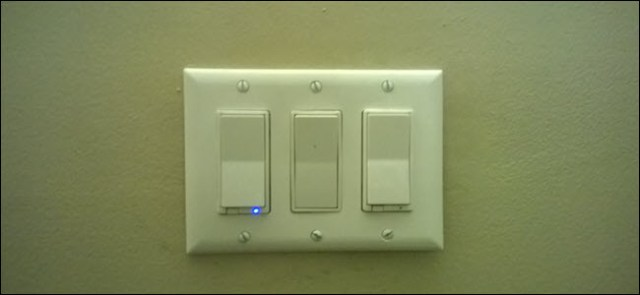 Two smart switches and a standard paddle switch between them.