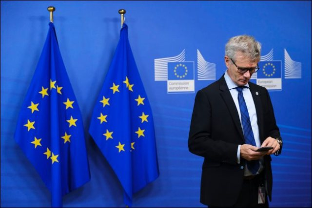 A man using a smartphone with two EU flags behind him.