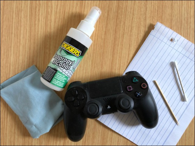 A DualShock 4 controller sitting on a piece of paper next to a toothpick, a Q-tip, an isopropyl alcohol spray and a cloth.