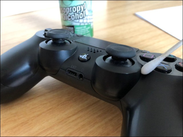 A DualShock 4 controller with a Q-tip above it next to a bottle of isopropyl alcohol.
