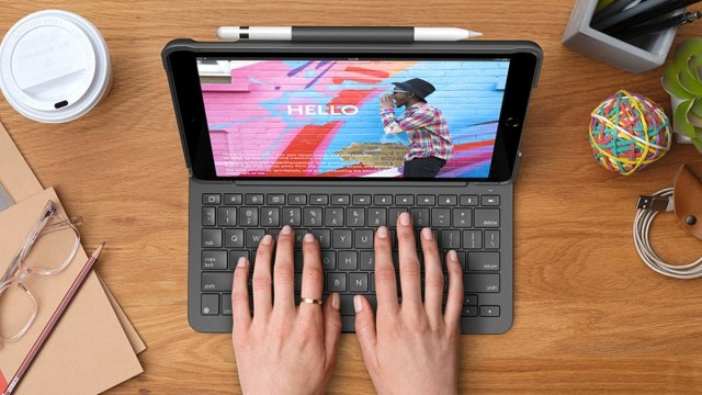 A photo of a person using the Logitech Slim Folio case for iPad.