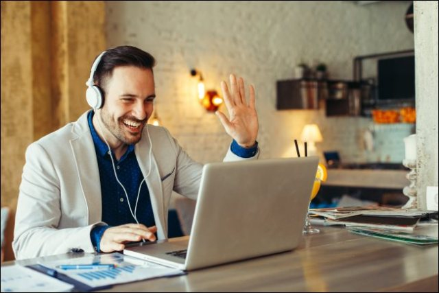 A man wearing headphones and waving his laptop.