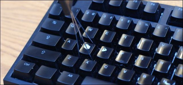 A cap removal tool prepares to remove a key from a keyboard.