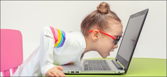 Kid with glasses leaning on laptop