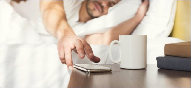 A man asleep in bed reaching for a smartphone on a bedside table.