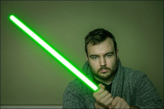 A composite photo of the author holding a lightsaber