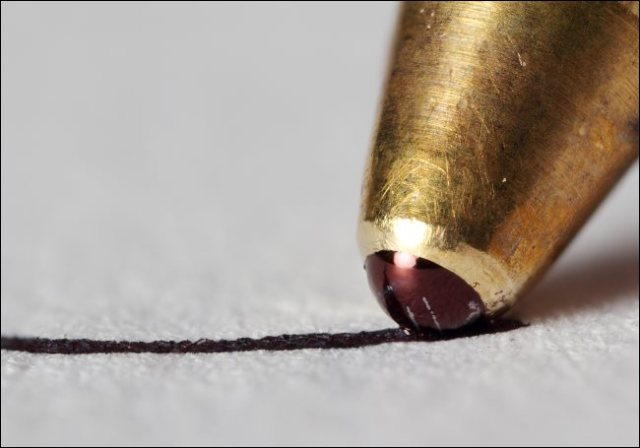 A macro photo of the tip of a ballpoint pen written on a piece of paper.