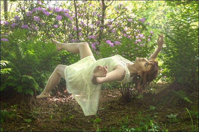 An outdoor photo of a woman who appears to be levitating on her back.