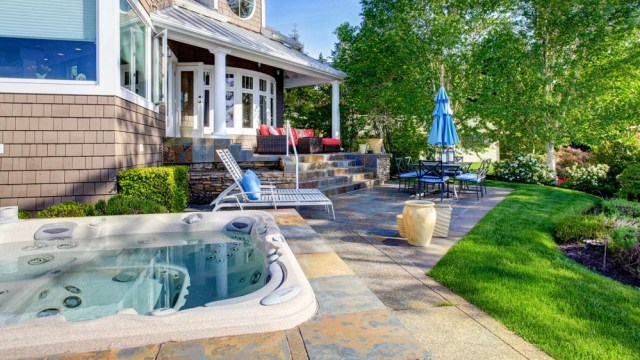 A beautiful house with garden furniture, beautiful landscaping and whirlpool.