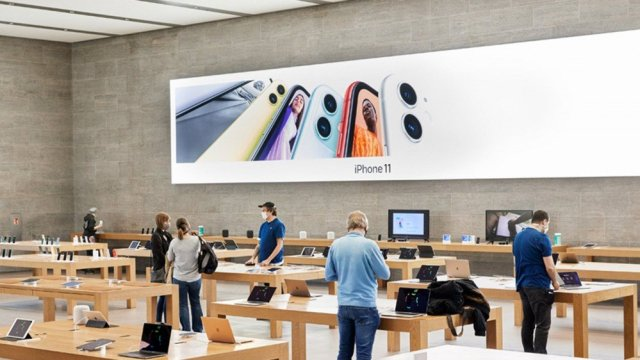 A sparsely populated Apple Store, with customers and employees wearing masks.