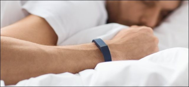 A man wearing an activity tracker on his wrist while sleeping in his bed.