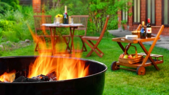 A backyard with fireplace, outdoor furniture and beverage cart.