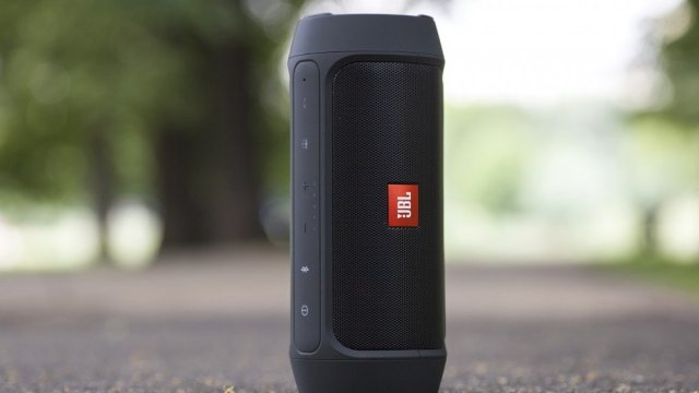 A photo of the JBL Charge 2 smart speaker on concrete.