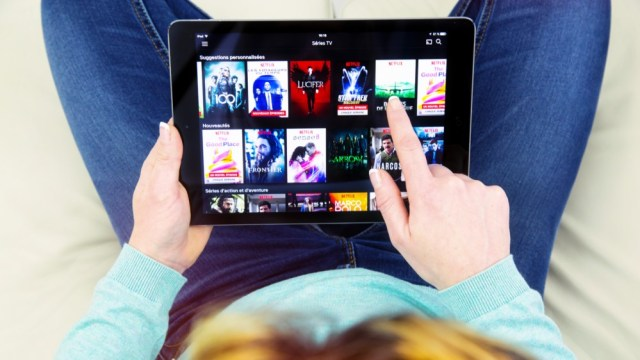 Woman sitting cross-legged on her sofa and using her tablet to watch movies online