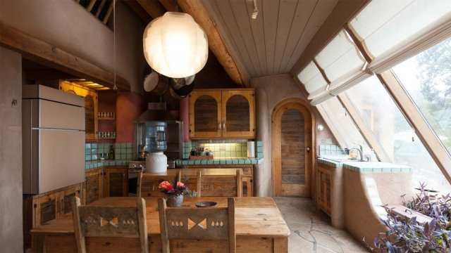 The interior of an Earthship home, showing organic designs, large windows and heavy use of stucco.