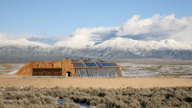 An Earthship sitting in the desert, against the backdrop of mountains and clouds.