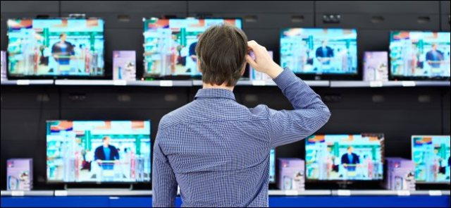 A man scratches his head while looking at a TV screen in a store.