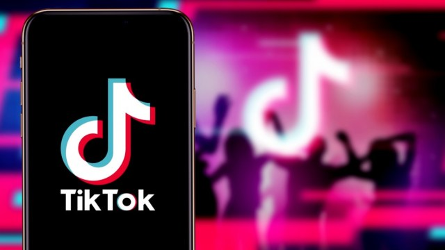 The TikTok app on iPhone in front of the TikTok logo and silhouettes of people partying