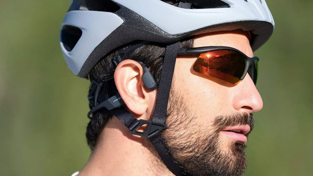 A man wearing the AfterShokz Mini helmet and a bicycle helmet.