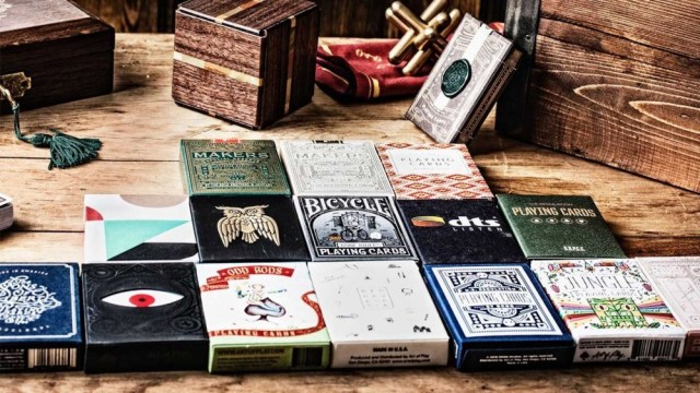 Fifteen packs of different playing card decks arranged in a pyramid shape on a wooden table.