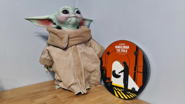 The bottom of a booth, showing stylized illustrations of the Mandalorian finding Baby Yoda