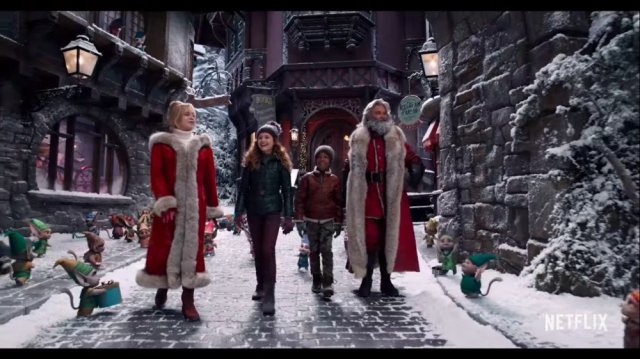 Father Christmas, Mrs. Claus and two children walk on a snowy village path.