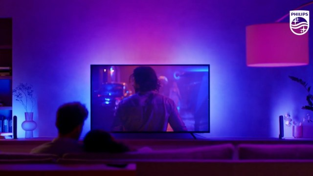 Philips Hue Play Gradient Lightstrip reflecting colors on the wall behind the TV, with a couple sitting on a sofa in the foreground watching them