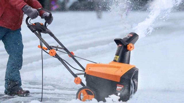 A person plowing the disc with a snow blower.