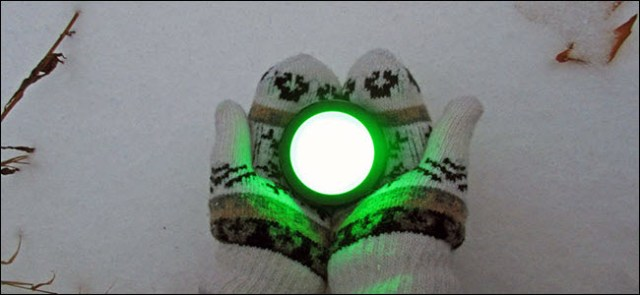 A pair of gloved hands holding a shiny green Echo button on snow.