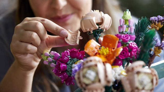 A person building a bouquet of LEGO flowers