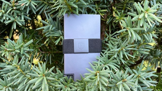 Ekster aluminum wallet sitting on a tree