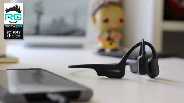 The Aftershokz Aeropex Mini on a desk with a phone in the foreground and Leatherface Pop in the background