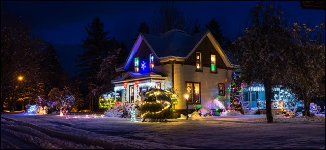 Private snow-covered house with bright Christmas lights and decorations