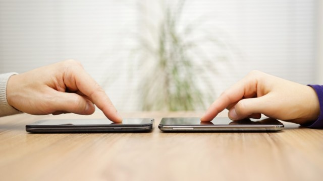 Two people sharing files on their smartphones