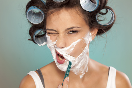 attractive young woman shaves her face