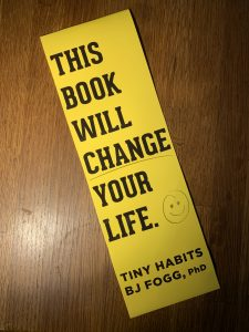 """""""This book will change your life. Tiny Habits by BJ Fogg, PhD"""" on a wood background"""