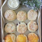 A box of assorted scones with a dish of butter and some flowers