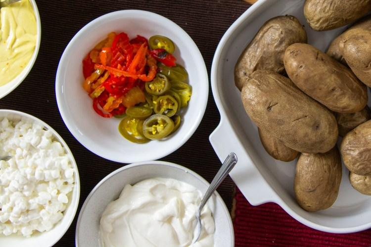 A pile of baked potatoes next to some small bowls of pickled peppers, sour cream, and cottage cheese